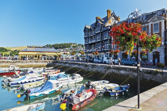 Colourful hanging baskets surround a tidal harbour in Dartmouth.