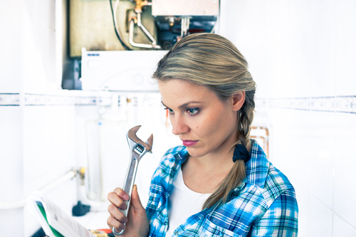 Beautiful Girl Is Trying To Repar a Boiler Using a Pipe Wrench