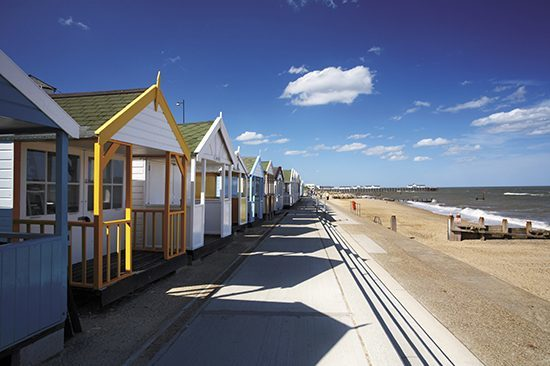 Southwold beach huts & pier on a summers day on the Suffolk Coast.