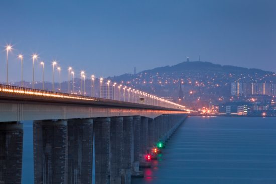 Long exposure of the Firth of Tay in the late afternoon November twilight. The Tay Bridge is iluminated by the rush hour traffic with beautiful Dundee in the distance. Long exposure shows the rivers blurred motion. Shot with Canon 70-200 and Canon 5D MK2. Tay