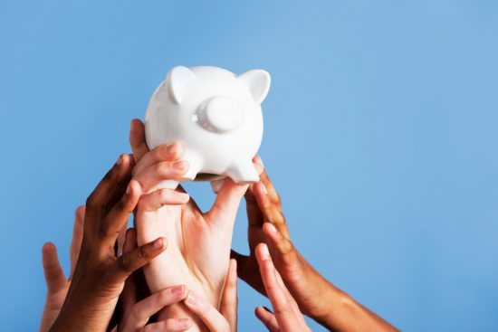 A group of hands all reach for a ceramic piggy bank held high against a blue background with plenty of copy space. envy