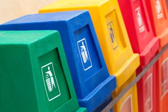 A row of recycling bins in different colors at a recycling station. Recycle