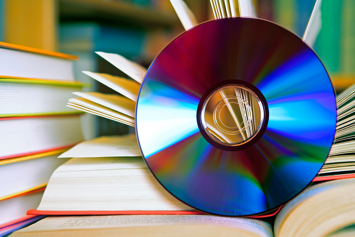 A DSLR photo of an open book with a CD in front of it. Some other books are visible at the background. Shallow depth of field. Can illustrate the concept of digital audio books instead of standard paper books. book to film adaptations