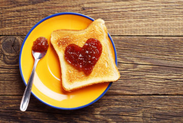 Toast bread with jam in shape of hearts on vintage wooden table. Top view. Happiness is like a jam sandwhich