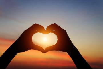 heart full of light silhouette hand gesture feeling love during sunset. heart full of light