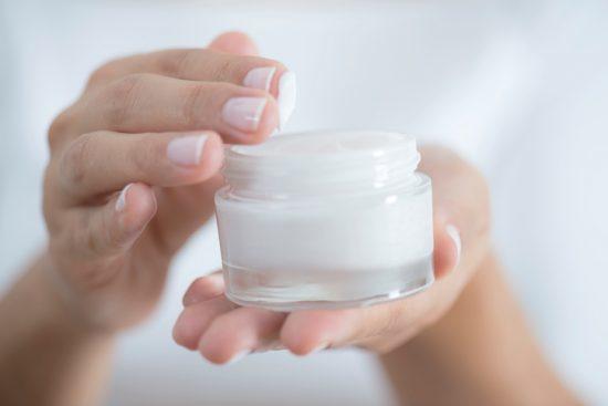 Female hand holding moisturizer in hand, horiztonal. moisturisers