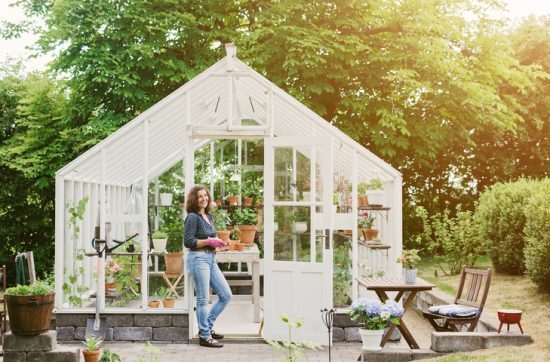 Beautiful woman gardening by her greenhouse. the september garden checklist