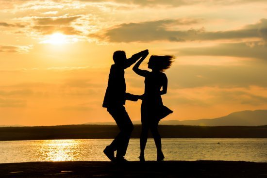 Couple silhouette dancing by the sea at sunset. dance