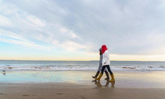 Friend: Two women walk next to the ocean at the Brighton Beach, Brooklyn, New York, USA.