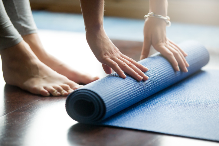 Close-up of attractive young woman folding blue yoga or fitness mat after working out at home in living room. Healthy life, keep fit concepts. Horizontal shot. Go