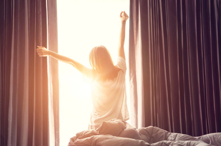 Woman standing near the window while stretching near bed after waking up with sunrise at morning, back view. dreams