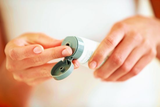 Cropped image of a young woman putting moisturizer onto her finger for dry skin
