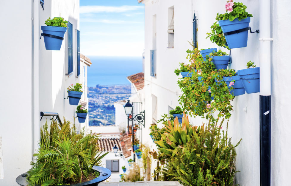 Picturesque street of Mijas with flower pots in facades. Andalusian white village. Costa del Sol. Southern Spain
