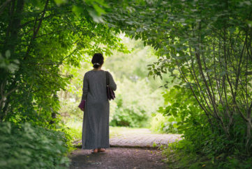 A middle aged woman walking through a tunnel of leaves in a peaceful and green summer garden. sanctuary