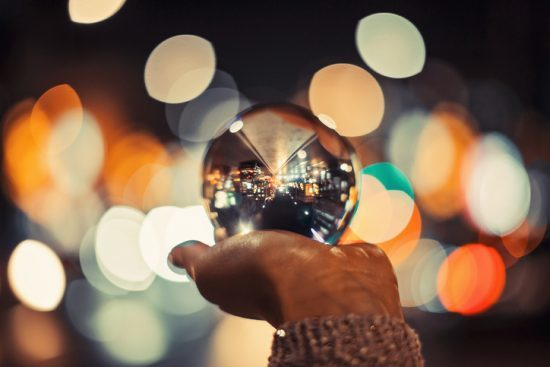 Girl in city holding crystal ball with beautiful bokeh . The art will go on
